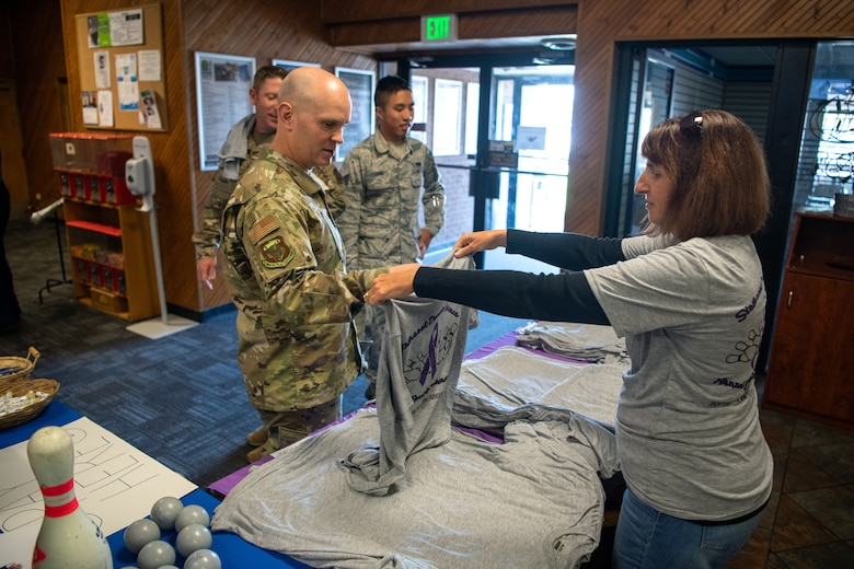 Master Sgt. Benjamin Davis, 50th Wing Staff Agency/ 50th Mission Support Group first sergeant, receives a free T-shirt during the Peterson Air Force Base Family Advocacy Program's second-annual Strike-Out Domestic Violence bowling tournament at the Bowling Center on Peterson AFB, Colorado, Oct. 1, 2019. The tournament was organized in support of National Domestic Violence Awareness Month, observed during the month of October. (U.S Air Force photo by Katie Calvert)