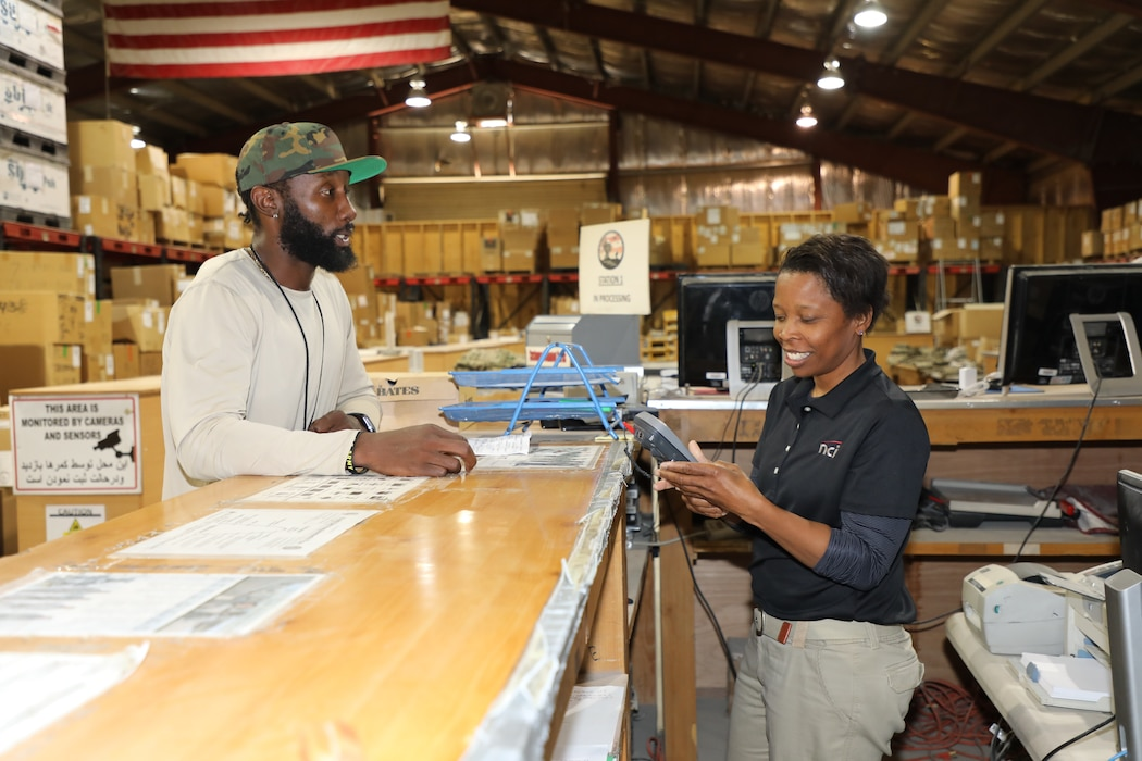 Logistics Management Specialist Jimmy Mapp orders supplies from Logistics Analyst Liz Johnson at a warehouse on Bagram Airfield, Afghanistan.  Mapp has worked for U.S. Army Corps of Engineers for six years and started his Afghanistan deployment as a 90-day assignment. He is now on his 10th month in country and has been promoted to a new job working in Information Technology for the Afghanistan District as a Contracting Officer Representative.