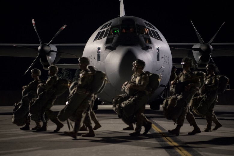 Airmen walk in front of a C-130J