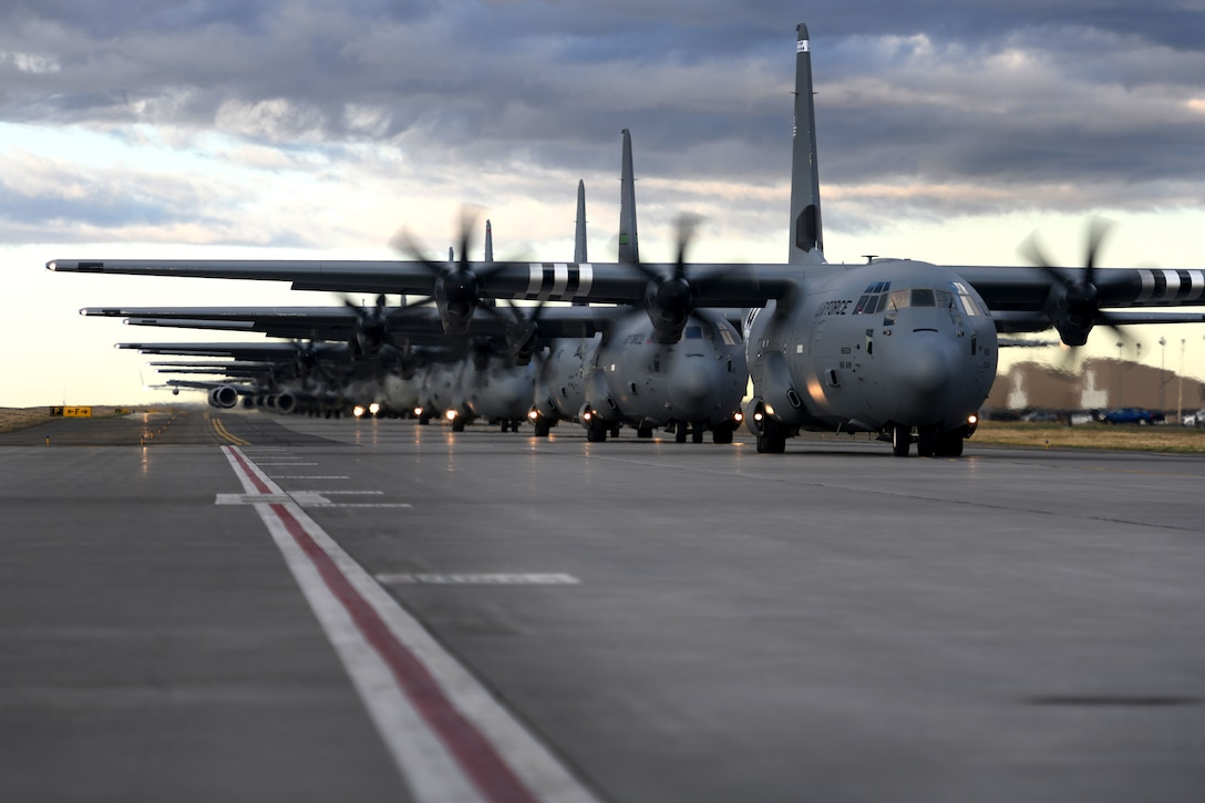 C-130s taxi down a runway in a formation.