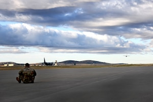 A man watches C-130s take off.