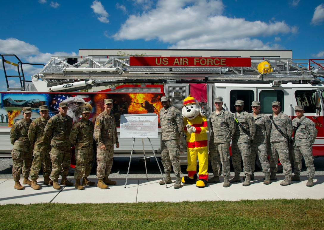 """Members of the 436th Airlift Wing leadership team and the 436th Civil Engineer Squadron fire department pose next to the recently signed proclamation declaring, """"October 6-12, 2019, Fire Prevention Week,"""" Oct. 4, 2019, at Dover Air Force Base, Del. This year's theme, """"Not Every Hero Wears a Cape. Plan and Practice Your Escape!"""" serves to educate the Dover AFB community about the importance of developing a home fire safety plan. (U.S. Air Force photo by Staff Sgt. Zoe Russell)"""