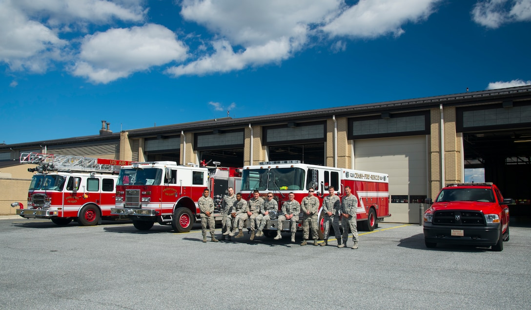 Members of the 436th Civil Engineer Squadron fire department pose next to their fire trucks Oct. 4, 2019, at Dover Air Force Base, Del. The firefighters were preparing for the upcoming Fire Prevention Week 2019, an annual weeklong observance to educate Dover AFB's community about the importance of fire prevention. (U.S. Air Force photo by Staff Sgt. Zoe Russell)