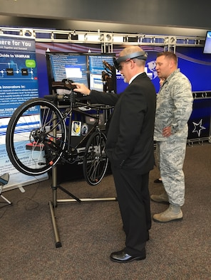 Dr. Michael Gregg (left), director of the Air Force Research Laboratory Aerospace Systems Directorate, uses a mixed-reality application to change the tire on a Wright Cycle Company bicycle as Capt. David Eisensmith guides the process. The demonstration, on display at the 2019 Air Vehicles Technology Symposium, is part of the Virtual, Augmented, and Mixed Reality for Aircraft Maintenance team's effort to show the technology's potential for future aircraft maintenance. (U.S. Air Force Photo)