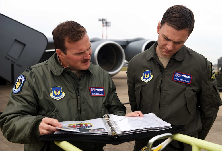 Capt. Ben Oakland, 351st Air Refueling Squadron aircraft commander, and 1st Lt. James Winegardner, 351st Air Refueling Squadron co-pilot, look over pre-flight checklists prior to takeoff during a readiness exercise at RAF Mildenhall, England, Oct. 3, 2019. Exercise scenarios were designed to ensure 100th ARW Airmen were fully prepared for potential contingencies in the wing's area of responsibility. (U.S. Air Force photo by Airman 1st Class Brandon Esau)