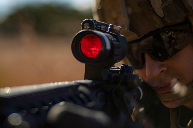 A soldier looks through a rifle scope with a red lens.