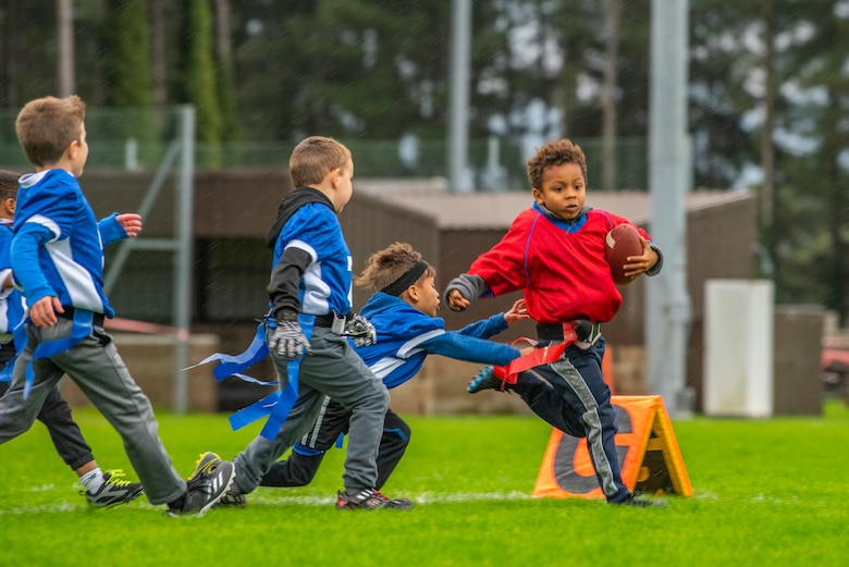 A flag football player sprints to avoid losing his flag at Heritage Park Oct. 7, 2019, at RAF Mildenhall, England. The park reopened following a six-month renovation. (U.S. Air Force photo by Airman 1st Class Joseph Barron)