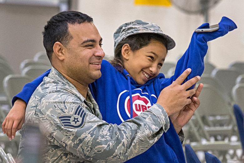 Staff Sgt. Luis Castillo, 434th Maintenance Squadron, shares laughs with his daughter Isabella Oct. 6, 2019 during the Grissom Fall Festival at Grissom Air Reserve Base, Indiana. The festival gave unit members and their families an opportunity to throttle back after a busy year of deployments, exercises, inspections and an airshow. (U.S. Air Force photo/Douglas Hays)