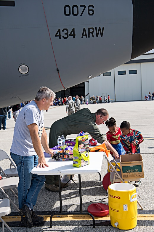 Lt. Col. Doug Perry, 434th Operations Support Squadron, left, and Lt. Col. Joe Austin, 72nd Air Refueling Squadron, help some young super heroes get candy Oct. 6, 2019 during a 'Tanker Treat' held during a fall festival at Grissom Air Reserve Base, Indiana. The festival gave unit members and their families an opportunity to focus on resiliency and throttle back after busy year of deployments, exercises, inspections and an airshow. (U.S. Air Force photo/Douglas Hays)