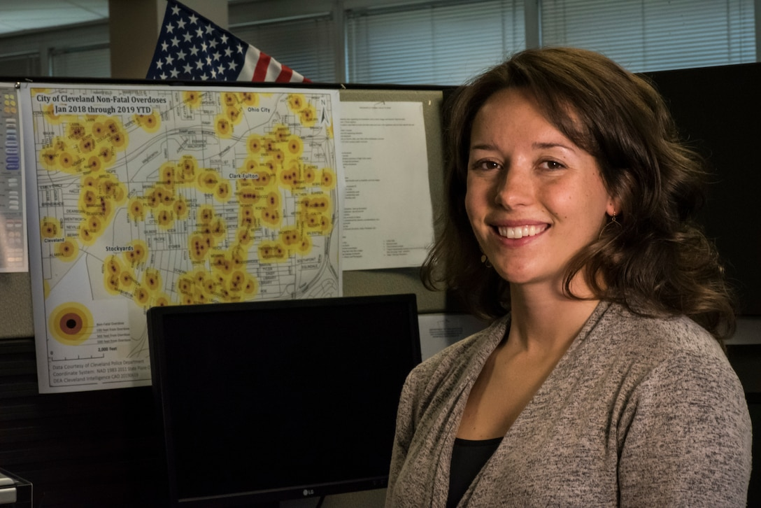 U.S. Air Force Staff Sgt. Carolyn Kinzel, a C-130H Hercules loadmaster assigned to the 179th Airlift Wing, Ohio Air National Guard, and an Ohio Air National Guard Counterdrug Task Force criminal analyst, poses in front of an overdose map she created Aug. 1, 2019, at the Drug Enforcement Administration (DEA), Cleveland, Ohio. The Ohio National Guard Counterdrug Task Force personnel provide support to law enforcement agencies and community based organizations in order to enhance efforts to counter and defeat the threat of illegal substances, trafficking and violence in Ohio. (U.S. Air National Guard photo by Airman 1st Class Alexis Wade)