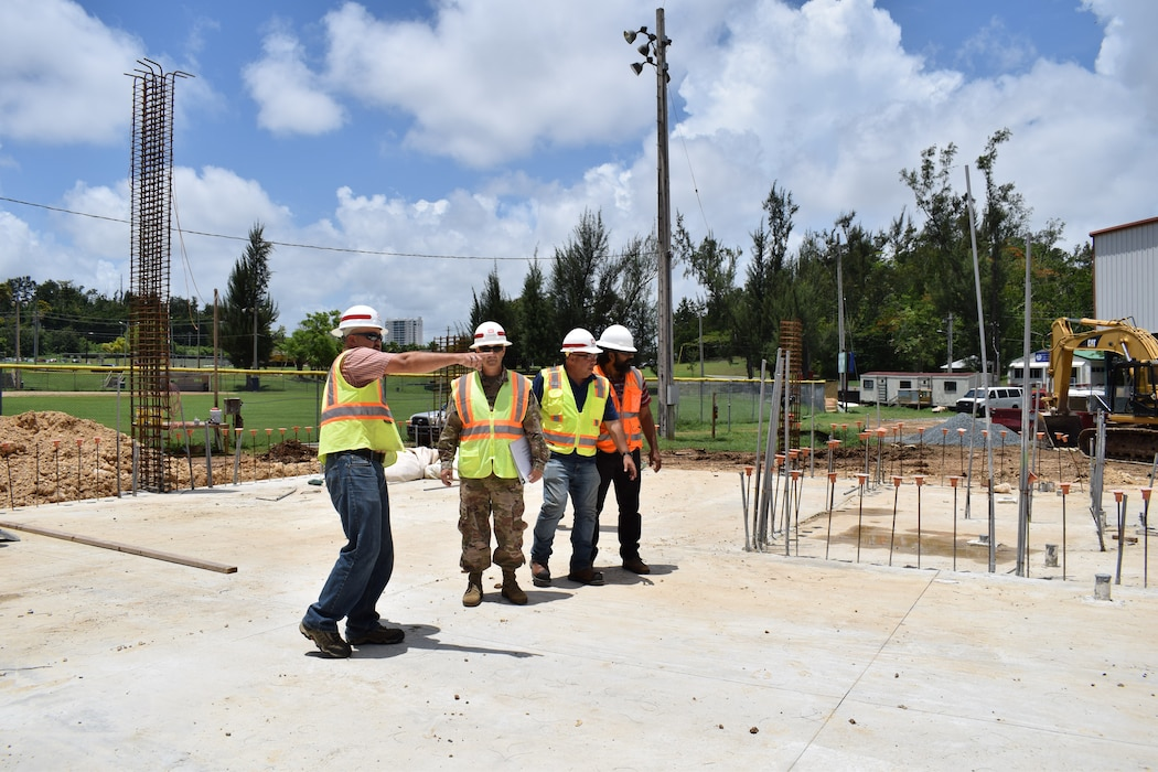 Four men wearing personal protective gear walk around a military construction site