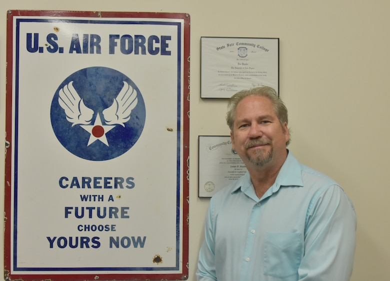Capital Improvements Branch Systems Safety Program manager at Arnold Air Force Base, stands by an Air Force recruitment sign from the 1940s he acquired while antiquing, which has been an interest of his for nearly 40 years. The sign has been displayed in every office Raabe has had since purchasing it. (U.S. Air Force photo by Bradley Hicks)