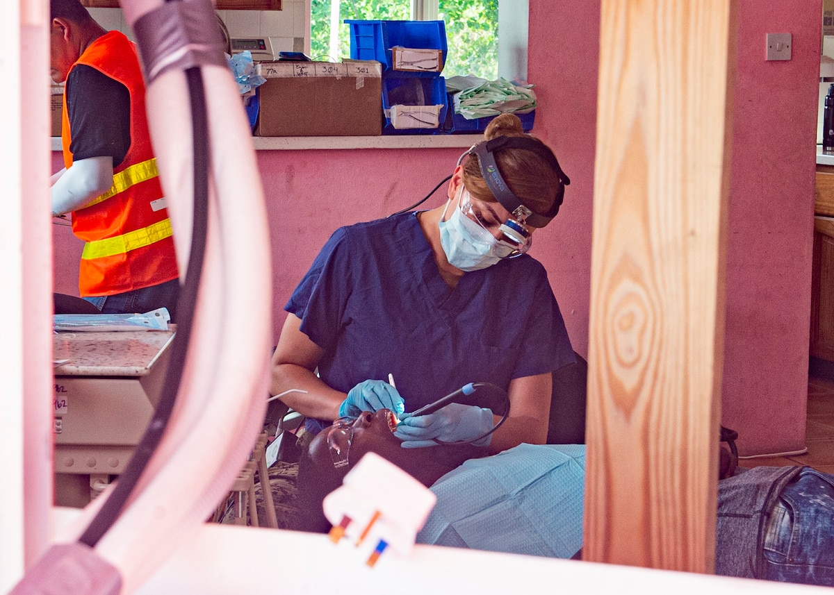 A dental technician cleans the teeth of a patient.