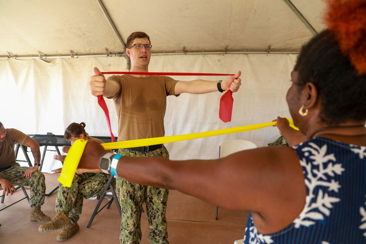 U.S. Navy Hospital Corpsman teaches a woman mobility exercises.