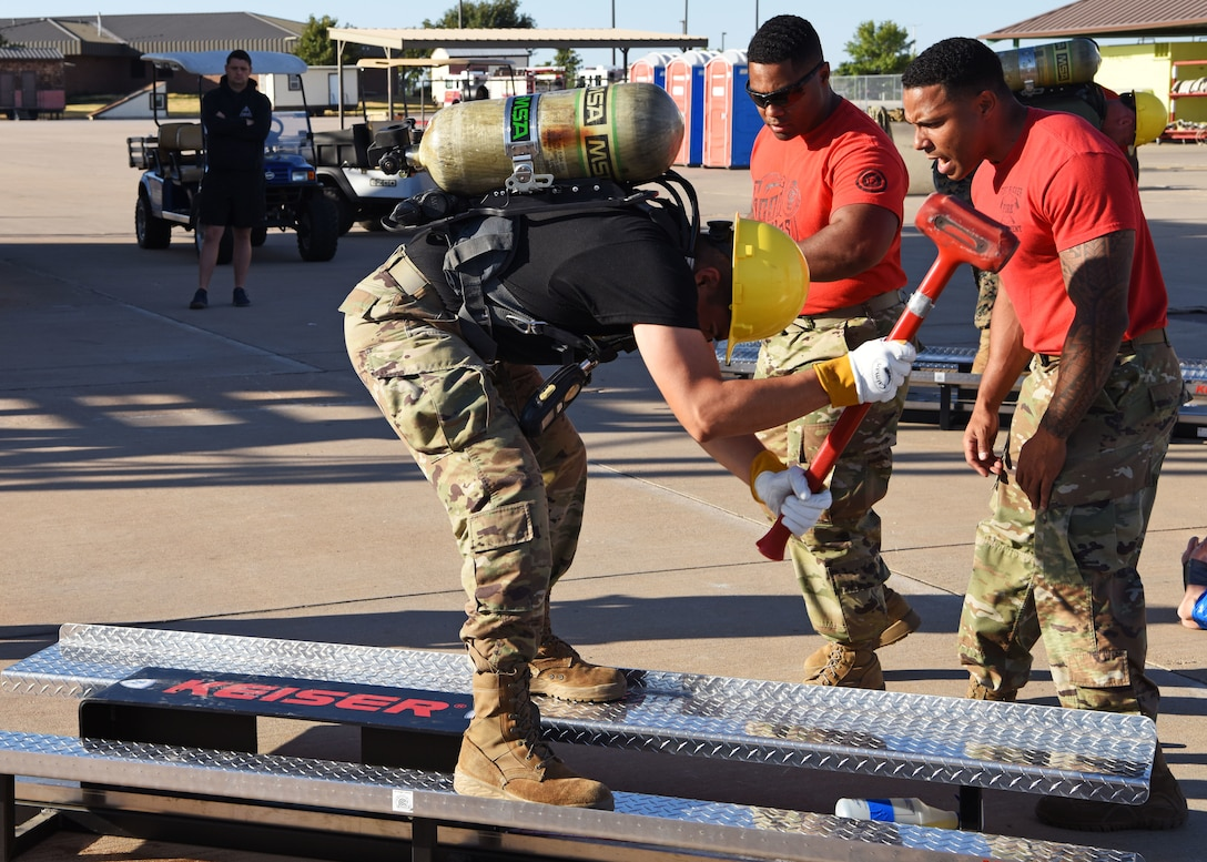 Fire prevention instructors motivate a fellow Soldier as he participates in a team relay involving different firefighter related challenges during Blood, Sweat, and Stairs at the Louis F. Garland Department of Defense Fire Academy on Goodfellow Air Force Base, Texas, Oct. 5, 2019. The relay required teams to work together by completing each challenge at maximum effort. (U.S. Air Force photo by Airman 1st Class Ethan Sherwood/Released)