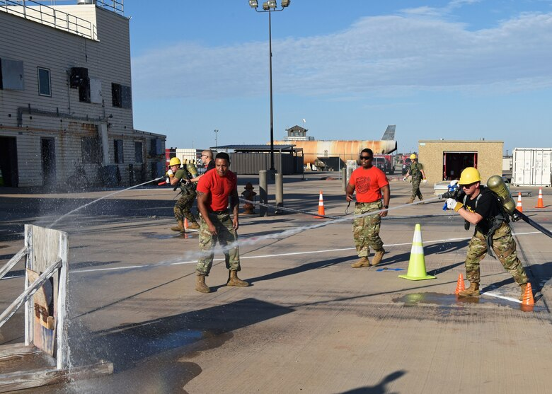 A U.S. Army Soldier fires a hose at a target after dragging it during Blood, Sweat, and Stairs at the Louis F. Garland Department of Defense Fire Academy on Goodfellow Air Force Base, Texas, Oct. 5, 2019. Though the challenges were meant to be fun, they were used to honor those involved in 9/11. (U.S. Air Force photo by Airman 1st Class Ethan Sherwood/Released)