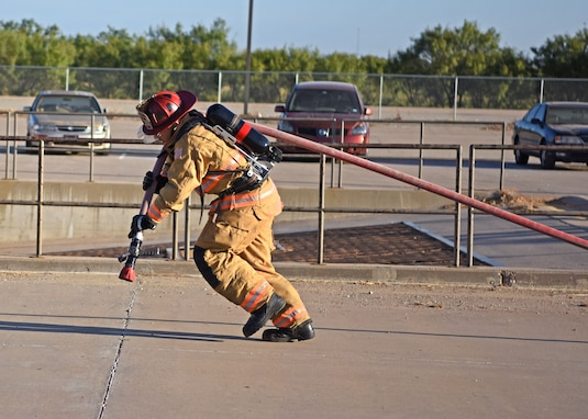 U.S. Air Force Tech. Sgt. Jordan Herrick, 312th Training Squadron instructor, drags a hose in full firefighting gear during the solo challenge at Blood, Sweat, and Stairs at the Louis F. Garland Department of Defense Fire Academy on Goodfellow Air Force Base, Texas, Oct. 5, 2019. During the solo challenge firefighters had to move heavy equipment and climb ladders as fast as possible. (U.S. Air Force photo by Airman 1st Class Ethan Sherwood/Released)