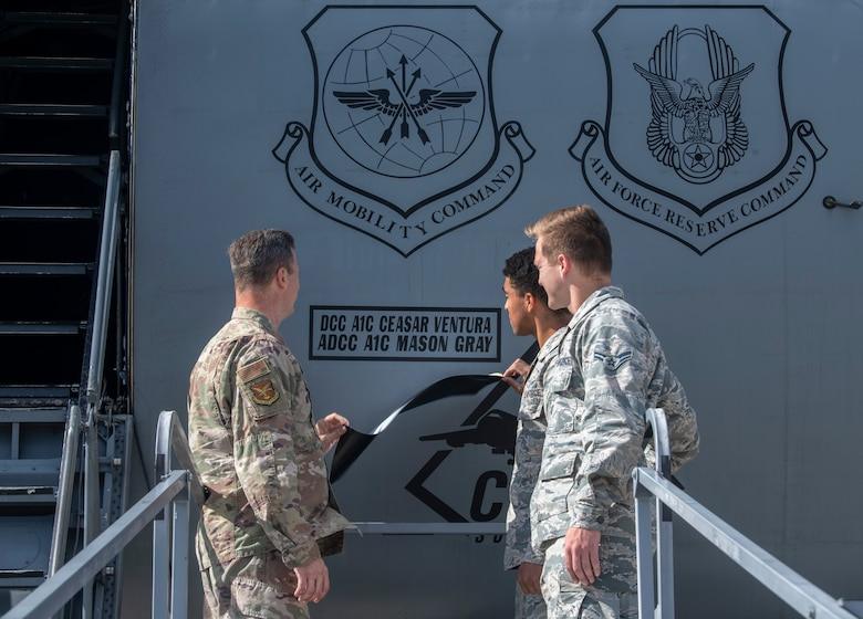 Col. Joel Safranek, 436th Airlift Wing commander, Airman 1st Class Ceasar Ventura, 436th Aircraft Maintenance Squadron dedicated crew chief, and Airman 1st Class Mason Gray, 436th AMXS assistant dedicated crew chief, pull off tape during a DCC unveiling ceremony Oct. 4, 2019, at Dover Air Force Base, Del. A change in policy marked the first time in approximately 20 years that the names of dedicated crew chiefs were unveiled on an Air Mobility Command C-5M Super Galaxy and C-17 Globemaster III.  (U.S. Air Force photo by Senior Airman Christopher Quail)