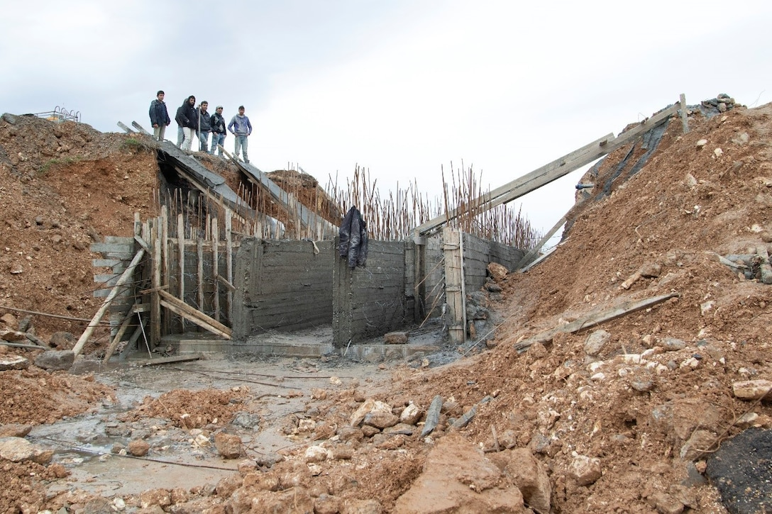 Syrian civilians look at remnants of bridge.