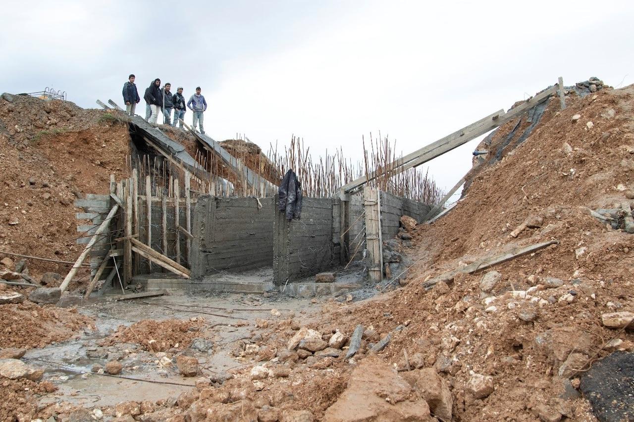 Syrian civilians look at remnants of bridge.