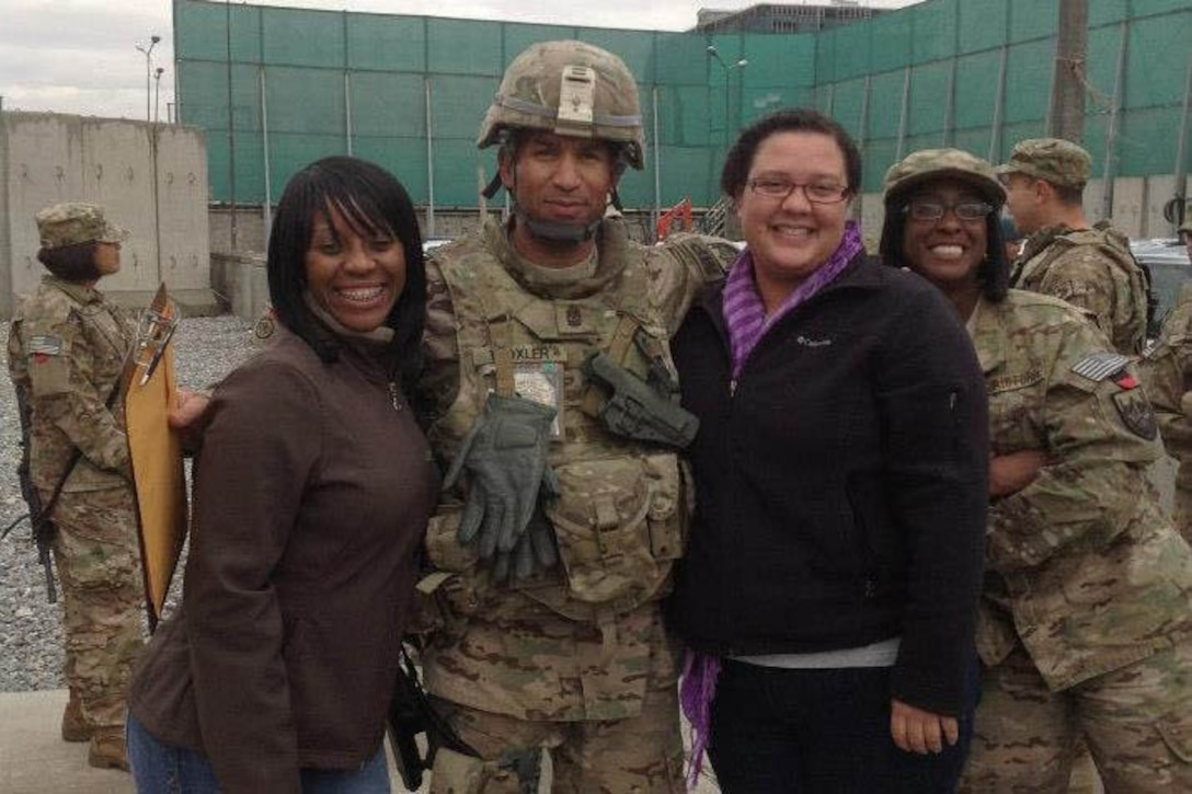 Two women pose for a photo with a man dressed in a military uniform.