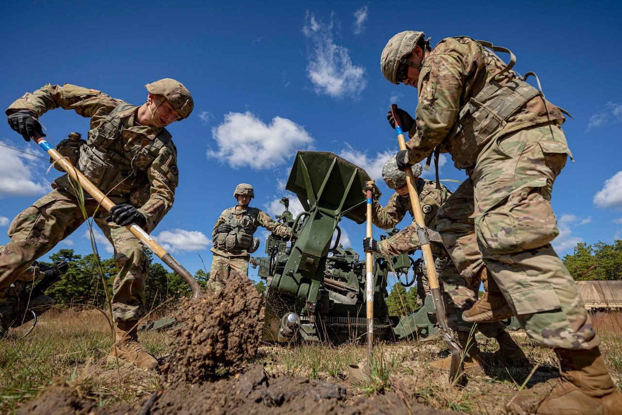 Soldiers dig a hole; some stand next to a howitzer.