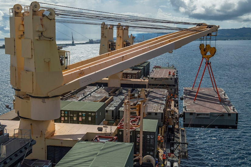A large cargo crane moves a container from a ship.