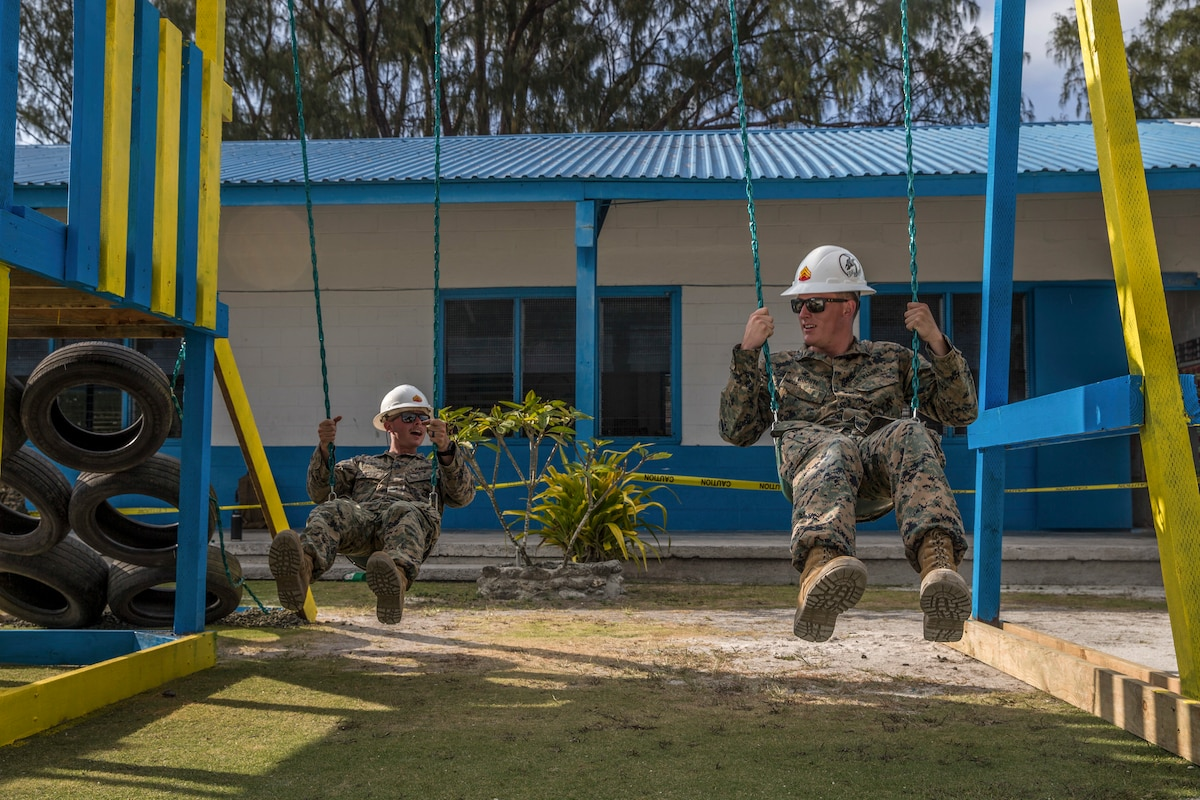 Two Marines in hardhats swing on a swing set.