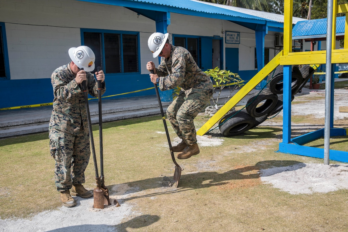 A Marine jumps on a shovel spade as another manipulates a tool in cement outside an elementary school.