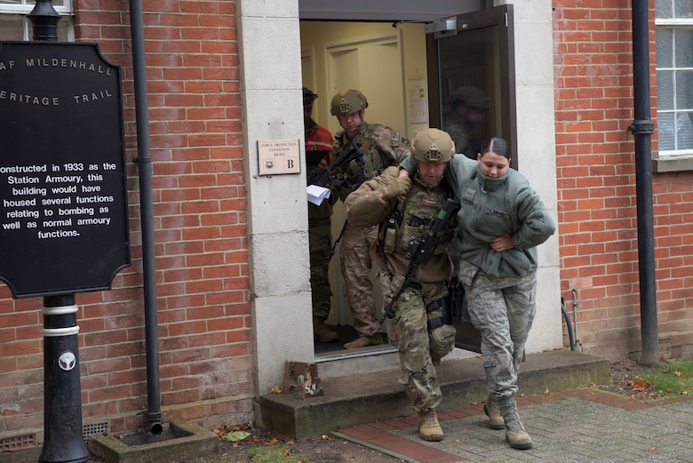 An Airman of the 100th Security Forces Squadron helps an injured victim during an active shooter training situation as a part of a readiness exercise at RAF Mildenhall, England, Oct. 4, 2019. Exercise scenarios were designed to ensure 100th ARW Airmen were fully prepared for potential contingencies in the wing's area of responsibility. (U.S. Air Force photo by Senior Airman Benjamin Cooper)