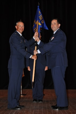 U.S. Air Force Col. Abraham Jackson, 480th Intelligence, Surveillance and Reconnaissance Group commander, presents the guidon to Lt. Col. James Fagan, 451st Intelligence Squadron, during an assumption of command ceremony in Signal Theater at Fort Gordon, Georgia, July 11, 2019. The 451st IS was stood up in order to conduct and execute Air Force and national analysis and reporting capabilities using tactical and national resources to provide intelligence products for U.S. Central Command, U.S. European Command and U.S. Southern Command operations, plans and forces, and the execution of Air Force national and tactical integration operations. (Courtesy photo)
