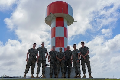 Air traffic control maintenance Marines with Headquarters and Headquarters Squadron pose in front of the new AN/FPN-68 Precision Approach Radar's antenna Sept. 30, 2019 on Marine Corps Air Station Futenma, Okinawa, Japan. MCAS Futenma is the first Marine Corps Air Station to receive the new radar system. (U.S. Marine Corps photo by Lance Cpl. Brennan J. Beauton