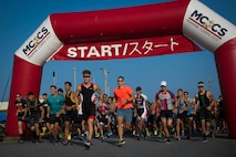 Runners consisting members of the U.S. and local communities begin the running portion of the 2019 Futenma Triathlon on Marine Corps Air Station Futenma, Okinawa, Japan, Oct. 6, 2019. The triathlon is held in order to strengthen the relationship between U.S service members and residents of Okinawa through athletic events. (U.S. Marine Corps photo by Cpl. Samuel Brusseau
