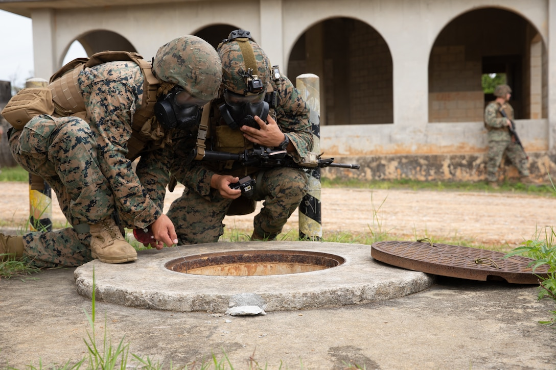 U.S. Marine Corps Cpl. Kyle Wielkie and Sgt. Jonathan Whitby lower atmospheric and chemical agent detectors into a storm drain to check for toxic or hazardous conditions during an explosive ordnance disposal exercise at Camp Hansen, Okinawa, Japan, Sept. 18, 2019. The EODEX was designed to simulate conventional warfare and the use of conventional ordnance and involved the participation of three U.S. military branches and over 43 different military occupational specialties within III Marine Expeditionary Force. Wielkie, a native of Lexington, South Carolina, is a chemical, biological, radiological and nuclear defense specialist with CBRN Defense Platoon, Headquarters Company, Headquarters Battalion, 3rd Marine Division and Whitby, a native of Tempe, Arizona, is an EOD technician with EOD Company, 9th Engineer Support Battalion, 3rd Marine Logistics Group.