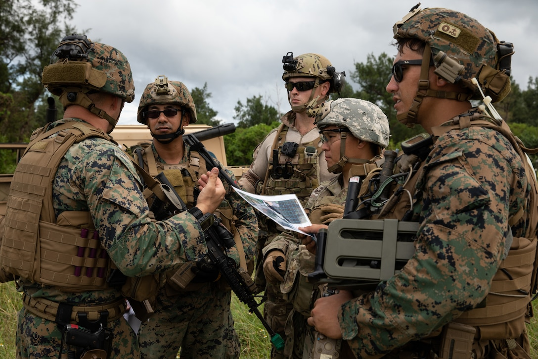 U.S. service members discuss a land mine scenario during an explosive ordnance disposal exercise at Kin Blue Training Area, Okinawa, Japan, Sept. 19, 2019.  The EODEX was designed to simulate conventional warfare and the use of conventional ordnance and involved the participation of three U.S. military branches and over 43 different military occupational specialties within III Marine Expeditionary Force.
