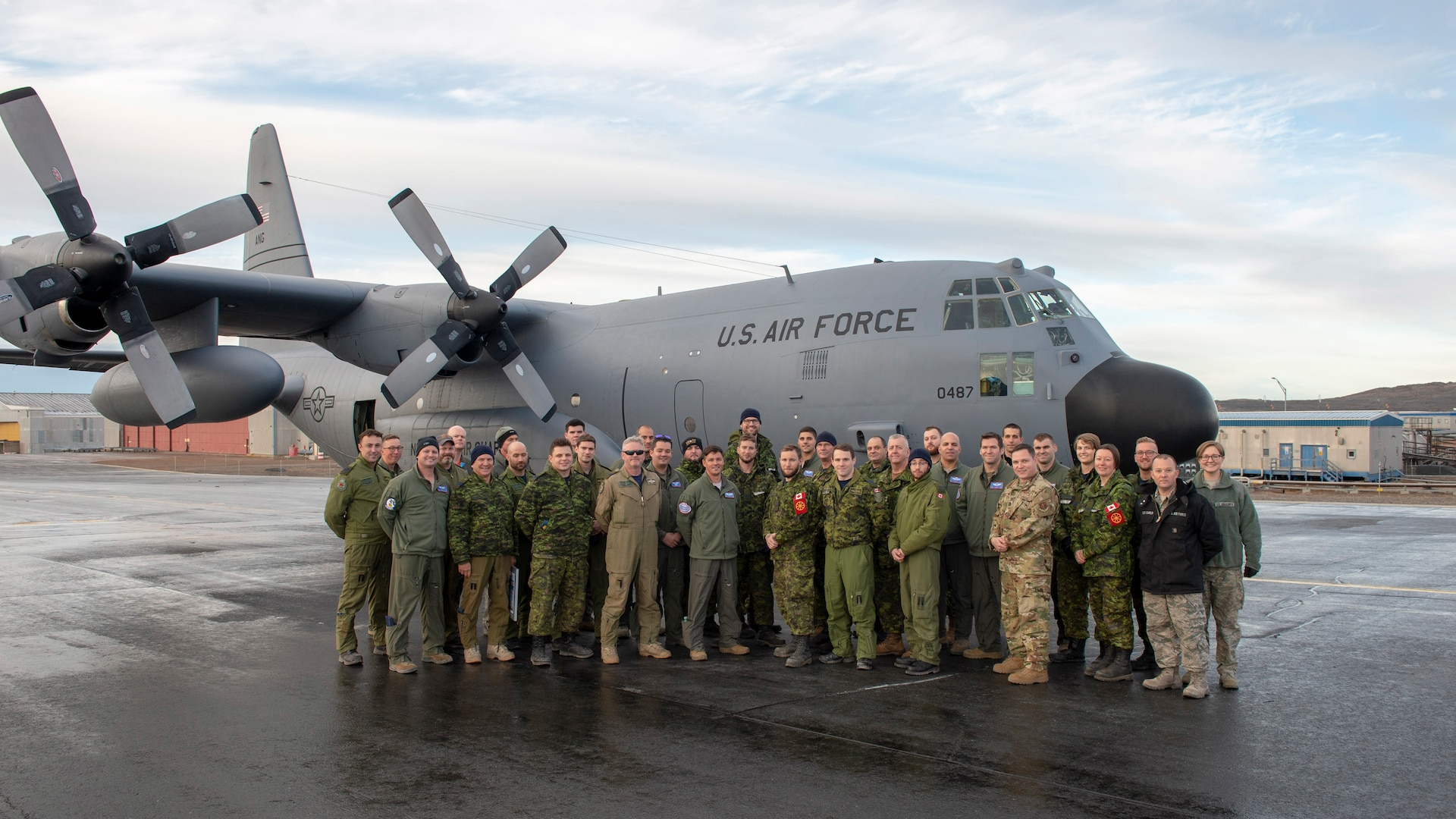 New York Air National Guard Airmen from the 109th Airlift Wing and Royal Canadian Air Force Airmen from 8 Wing in Trenton, Ontario, teamed up to resupply Canadian Forces Station Alert as part of Operation Boxtop. they are shown in front of a New York Air National Guard C-130 at Thule Air Base, Greenland, Oct. 3, 2019.