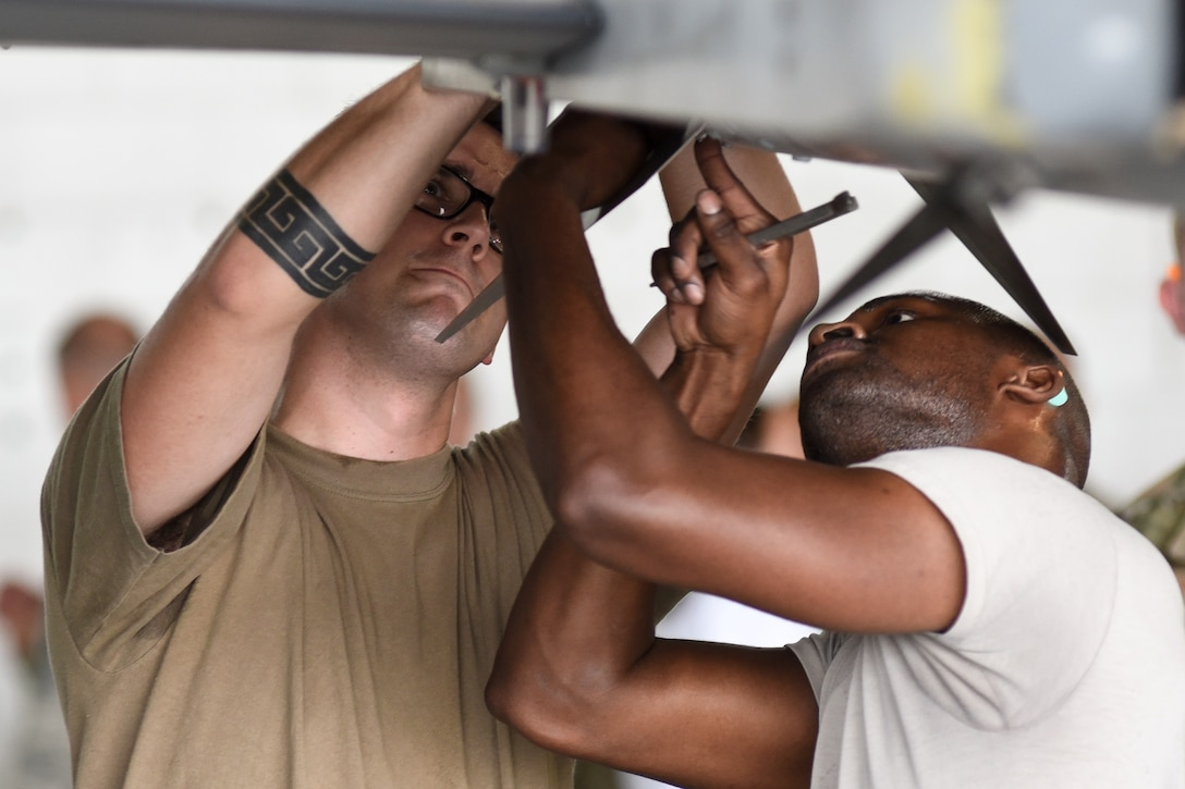 U.S. Air Force Staff Sgt. Demetrious Moutos, left, Senior Airman Josef Thompson, 77th Aircraft Maintenance Unit (AMU) load crew members work together to finish loading munitions on an F-16CM Viper during the quarterly load crew competition at Shaw Air Force Base, South Carolina, Oct. 7, 2019.