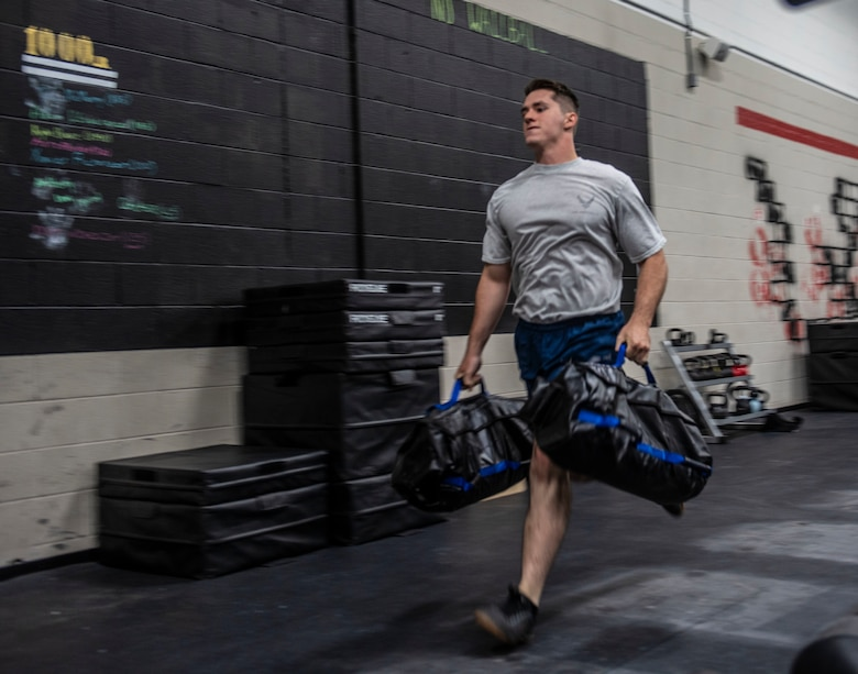 U.S. Air Force Senior Airman Zachary Stringer, 20th Civil Engineer Squadron, Explosive Ordnance Disposal (EOD) flight technician, runs with sandbags during a Tier 2 physical fitness practice test at Shaw Air Force Base, South Carolina, Oct. 4, 2019.