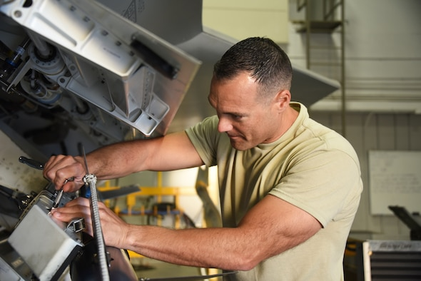 Armament apprentice course student, loads an AIM-9 into the side weapons bay of an F-22 at Sheppard Air Force Base