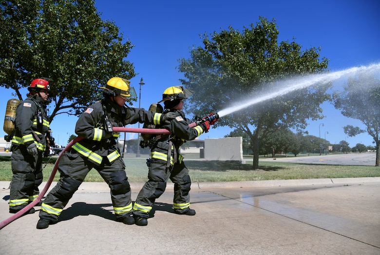 """Firefighters from the 22nd Civil Engineering Squadron practice water attack patterns Sept. 23, 2019, at McConnell Air Force Base, Kan. The exercise consists of spraying water in """"T"""" and """"O"""" patterns in order to cool the air while simultaneously extinguishing the fire. (U.S. Air Force photo by Airman 1st Class Nilsa E. Garcia)"""