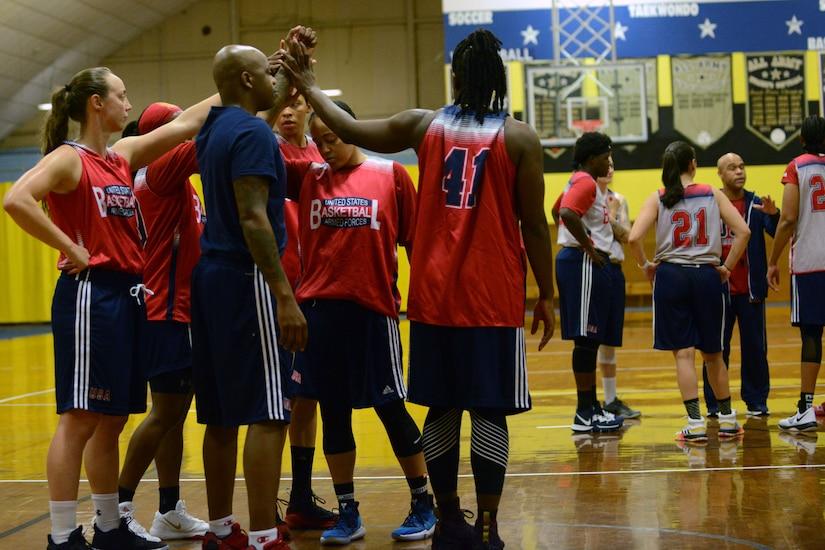 A women's basketball team put their hands together.