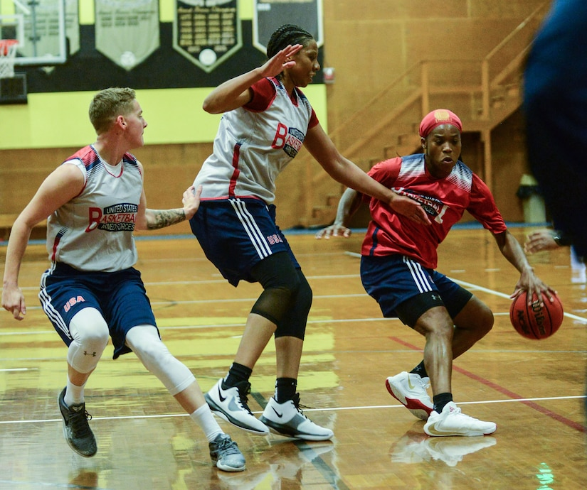 A woman dribbles past two defenders.