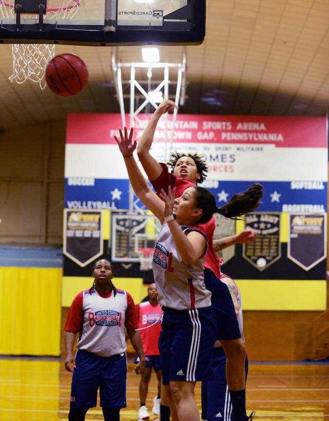 Women basketball players battle for a rebound.