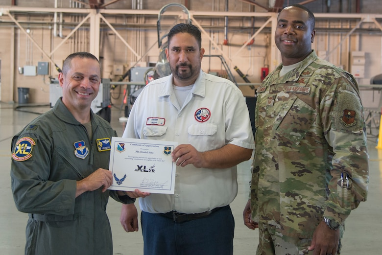 """Daniel Soto, a 47th Maintenance Directorate aircraft maintenance supervisor, receives an award from Col. Lee Gentile, 47th Flying Training Wing commander, and Command Chief Master Sgt. Robert Zackery III, 47th FTW command chief at Laughlin Air Force Base, Texas, Oct. 3, 2019. Soto was chosen by wing leadership to be the """"XLer of the Week"""" of Sept. 30, 2019. (U.S. Air Force photo by Senior Airman Daniel Hambor)"""