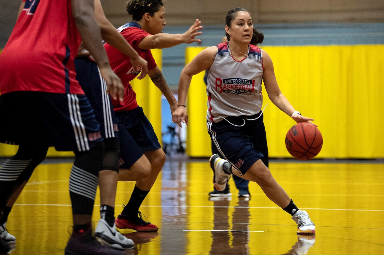 Woman dribbles a basketball as two opponents try to guard her.