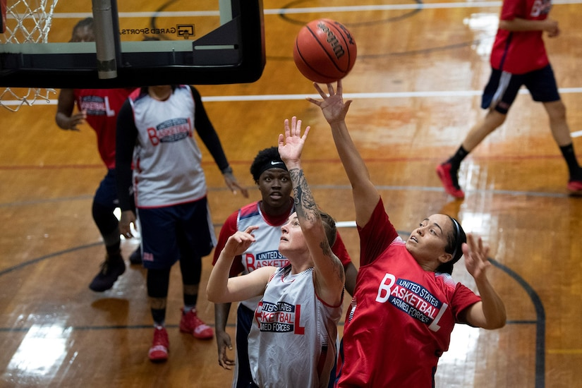 Woman jumps to shoot near the basket as a defender tries to block the shot.