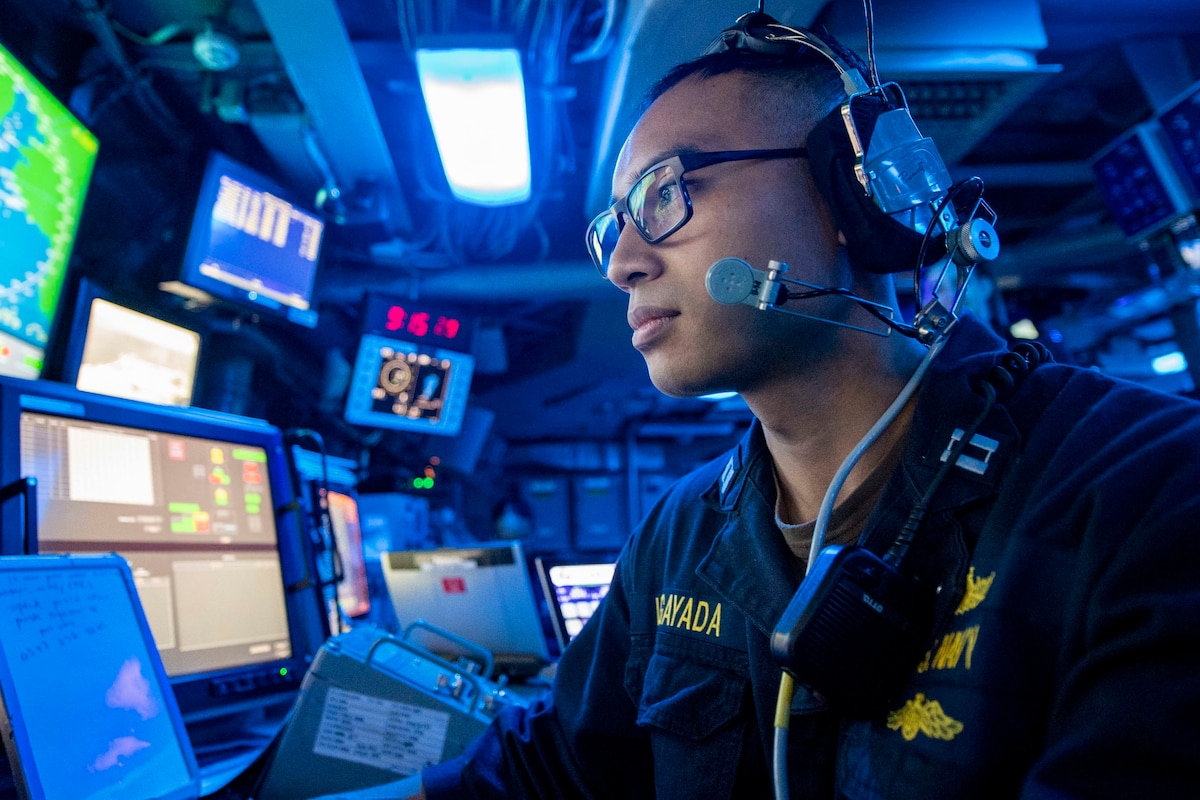 A sailor mans the control room bathed in blue light on a ship.