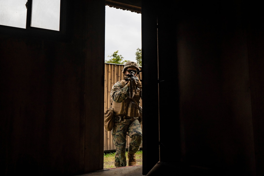 A Marine walks through a door while pointing a weapon.