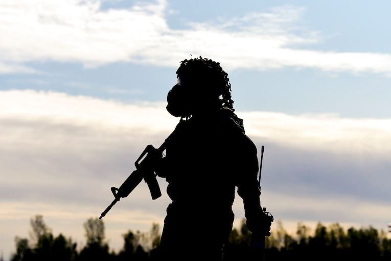 A silhouette of an airman walking with a weapon.