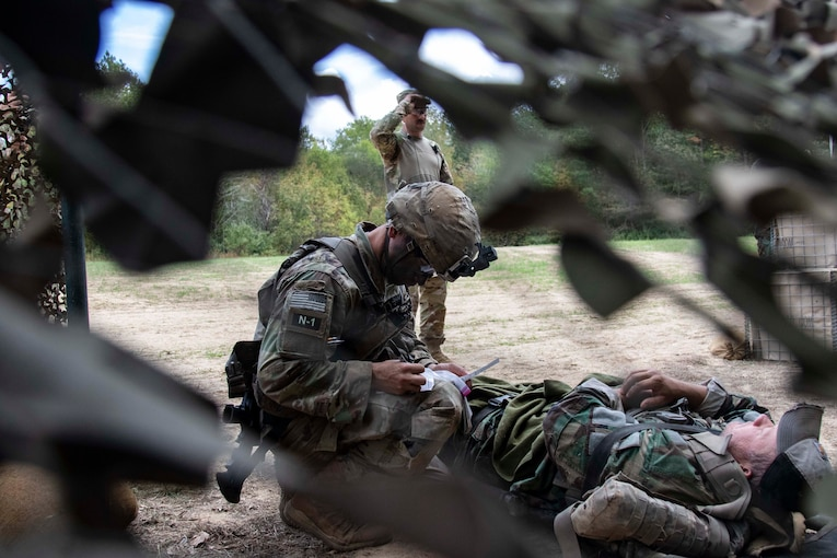 A soldier kneels on the ground to evaluate another soldier.